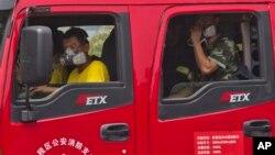 Nhân viên cứu hỏa Trung Quốc đeo khẩu trang khi đến hiện trường vụ nổ ở Thiên Tân.