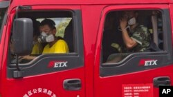 Chinese firefighters wear masks as they wait in their truck near the site of an explosion in northeastern China's Tianjin municipality, Aug. 15, 2015.