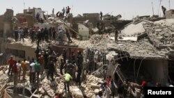 Cư dân đứng tại hiện trường một căn nhà bị hư hại sau vụ ném bom nhầm vào một khu phố phía đông thủ đô Baghdad, ngày 6/7/2015.