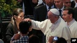 El Papa toca la cabeza de una niña a su llegada al Mall of Asia en Manila, este viernes, 16 de enero, de 2015.