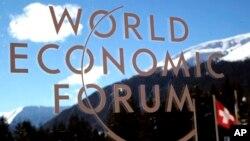 El logo del Foro de Davos visto através de una ventana con el fondo de los alpes suizos.