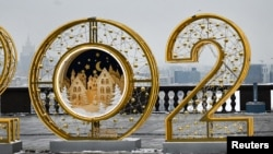 A man walks past large numbers for the upcoming year 2021, as part of Christmas and New Year decorations at Vorobyovy Hills observation point in Moscow on December 14, 2020. (Photo by Alexander NEMENOV / AFP)
