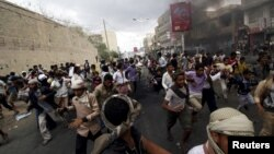 Anti-Houthi protesters run as pro-Houthi police troopers open fire in the air to disperse them, in Yemen's southwestern city of Taiz, March 23, 2015.
