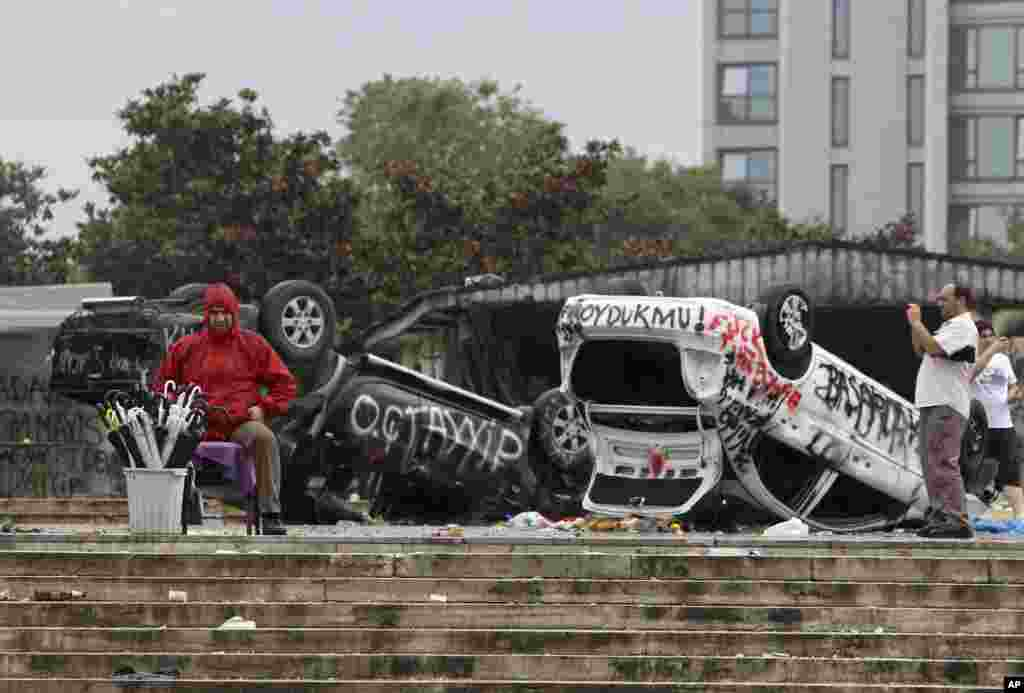 A street vendor sells umbrellas in front of destroyed police cars at the Taskim square in Istanbul, Turkey. Protests in Istanbul and several other Turkish cities appear to have subsided, after days of fierce clashes following a police crackdown on a peaceful gathering as protesters denounced what they see as Prime Minister Recep Tayyip Erdogan's increasingly authoritarian style.
