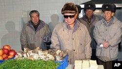 北韩领导人金正日(中)视察一家工厂