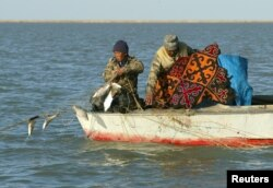 Kazakh fishermen pull a fishing net from a boat at Kokaral near the village of Karateren, southwestern Kazakhstan. Once the world's fourth largest lake, the Aral has shrunk so much that it has now split into two separate bodies of water.