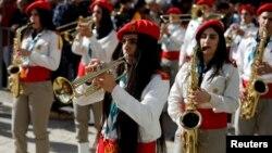 Para anggota marching band Palestina ikut memeriahkan parade untuk merayakan Natal di Lapangan Manger, di luar gereja Nativity, Bethlehem, Tepi Barat, Senin (24/12).