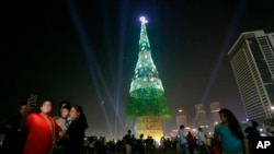 A Sri Lankan family takes photographs standing near an enormous artificial Christmas tree as others gather in Colombo, Sri Lanka, Dec. 24, 2016. Sri Lanka has unveiled a towering Christmas tree, claiming to have surpassed the world record for the tallest