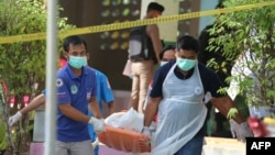Paramedics take away a body after four Thai civil defense volunteers were shot and killed outside of a school in the restive southern province of Pattani, Thailand, Jan. 10, 2019.