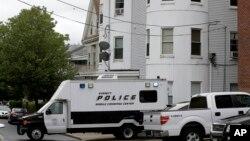 Kendaraan polisi di depan sebuah rumah bertingkat di Everett, Mass., yang digeledah terkait penembakan seorang tersangka oleh polisi di Boston (2/6). (AP/Steven Senne)