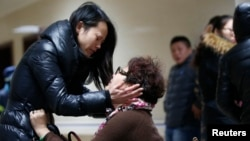 Relatives of a victim wait nervously at a hospital where people injured in a New Year's stampede are treated in Shanghai, Jan. 1, 2015.