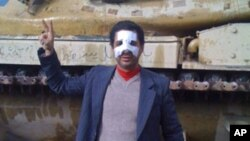 One of the organizers of the protests in Egypt, Ahmed Saleh stands in front of a tank with a bandaged broken nose he sustained during the uprising