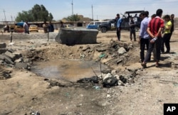 FILE - Civilians inspect a crater caused by a car bombing at an open-air market selling fruit, vegetables and meat in Baghdad's southeast suburb of Nahrawan, Iraq, April 30, 2016. The Islamic State group claimed responsibility for a bombing.