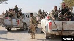 Pejuang Syiah dan tentara Irak berpatroli di Jurf al-Sakhar (25/10). Seorang pembom bunuh diri menyerang pos keamanan di pinggiran kota ini, menewaskan 11 orang dan melukai 23 lainnya, Senin (27/10).