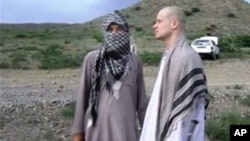 FILE - In this image taken from video obtained from the Voice of Jihad website in June 2014, Army Sgt. Bowe Bergdahl, right, stands with a Taliban fighter in eastern Afghanistan.