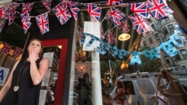 Employee Hayley Simmonds reacts as she celebrates the news that Britain's Catherine, Duchess of Cambridge, has given birth to a son, outside the British themed restaurant Tea & Sympathy in New York, Jul. 22, 2013.