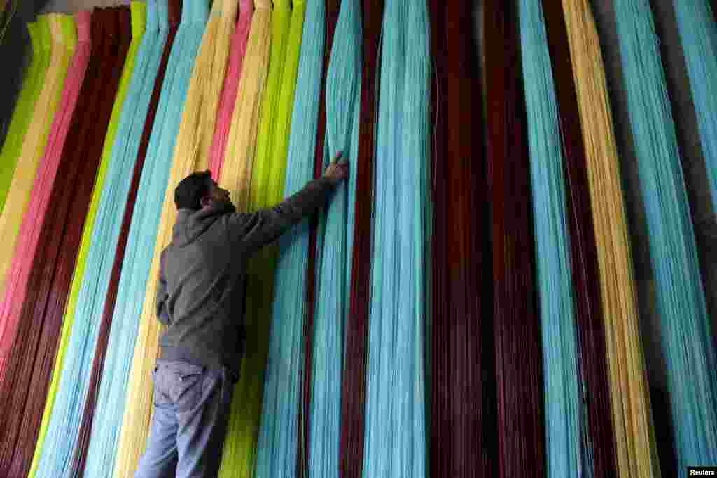 A man adjusts plastic strings, used to produce mats, inside a mat factory in the rebel-controlled area of Maarshureen town in Idlib province, Syria.