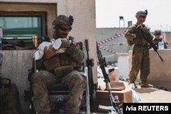 美国海军陆战队公布的照片显示,在喀布尔哈米德·卡尔扎伊国际机场的撤离行动期间,一名海军陆战队员抱着一名婴儿。(2021年8月20日)