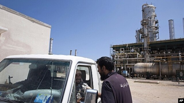 A Libyan worker talks with rebels in a vehicle as they patrol an oil refinery controlled by anti-Gadhafi forces on the western outskirts of Zawiya, Libya, Aug. 19, 2011