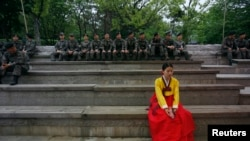 A woman in a traditional Korean Hanbok costume sits in front of South Korean soldiers at Namsangol Hanok Village in Seoul, May 20, 2013.