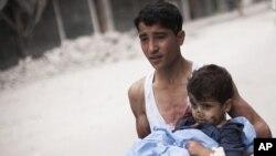 Một thanh niên Syria bồng một bé trai bị thương trong vụ pháo kích của quân đội chính phủ gần bệnh viện Dar El Shifa ở Aleppo