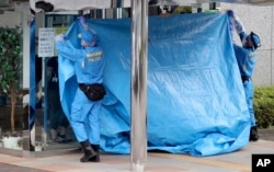 Police investigators cover the entrance of the Tsukui Yamayuri-en, a facility for the disabled where a number of people were killed and dozens injured in a knife attack, with a blue sheet in Sagamihara, outside Tokyo on July 26, 2016.