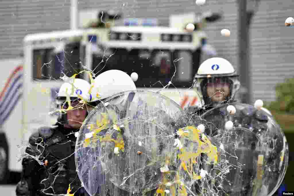 Eggs are thrown at policemen as farmers and dairy farmers from all over Europe take part in a demonstration, calling for more help with low prices and high costs, outside an emergency meeting of European Union farm ministers at the EU Council headquarters in Brussels, Belgium.