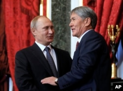 FILE - Russian President Vladimir Putin, left, welcomes Kyrgyzstan's President Almazbek Atambayev prior to a meeting of CSTO (Collective Security Treaty Organization) at the Kremlin, Moscow, Russia, Dec. 23, 2014.