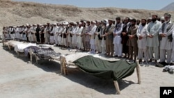 Afghan men offer funeral prayers near the bodies of 7 civilians killed, by a roadside bomb in the Alingar district of Laghman province, east of Kabul, Afghanistan, June 03, 2013.