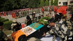 Indian Border Security Force officers carry the coffin of colleague Sushil Kumar who was killed in firing from the Pakistan side of the border, during a wreath-laying ceremony in Jammu, India, Oct. 24, 2016.