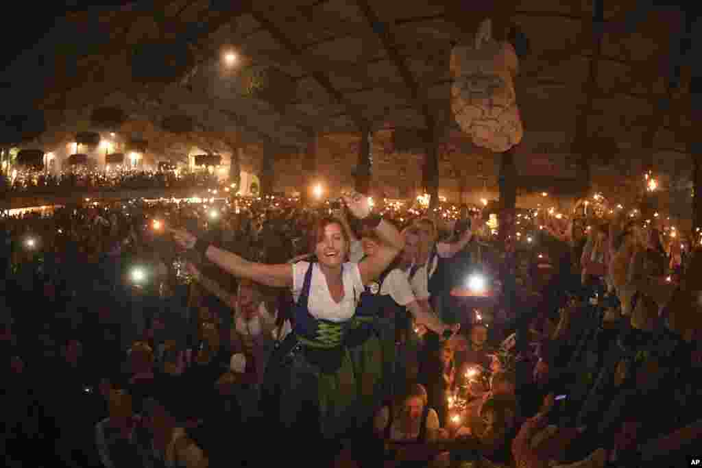 Waitresses celebrate after closing of a tent on the last day of the Oktoberfest beer festival in Munich, southern Germany, Oct. 3, 2017.