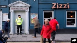 "FILE - A police officer stands outside an Italian restaurant in Salisbury, England, March 6, 2018, near the spot where former Russian double agent Sergei Skripal and his daughter were found critically ill March 4 following exposure to an ""unknown substance,"" later reported to be a nerve agent."