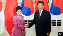 지난해 9월 중국 베이징을 방문한 박근혜 한국 대통령(왼쪽)이 시진핑 중국 국가주석이 인민대회당에서 가진 정상회담에 앞서 악수하고 있다. (자료사진)