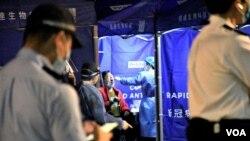 """港府1月26日晚首次在油麻地實施""""突襲式""""封區禁足強制新冠肺炎病毒檢測, 有受影響居民當晚在封鎖區內接受病毒檢測。(美國之音 湯惠芸拍攝)"""