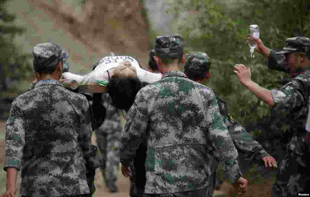 Paramilitary policemen carry an injured woman with a stretcher after an earthquake hit Ludian county of Zhaotong, Yunnan province. The magnitude 6.5 earthquake struck southwestern China, killing at least 175 people and leaving more than 180 missing and 1,400 injured in a remote area of Yunnan province, causing thousands of buildings, including a school, to collapse, Xinhua News Agency reported.