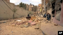 FILE - People walk amid the wreckage of damaged buildings in a street hit by shelling in Aleppo, Syria.