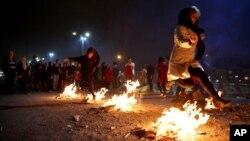 آگ کے تہوار کے موقع پر خواتین قدیم روایت کے مطابق جلتی آگ پر سے چھلانگ لگا رہی ہیں۔ فائل فوٹو