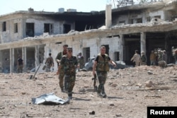 Forces loyal to Syria's President Bashar al-Assad walk at a military complex after they recently recaptured areas in southwestern Aleppo, Syria, in this handout picture provided by SANA on Sept. 5, 2016.