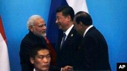 在中国东部山东省青岛举行的上海合作组织峰会上,印度总理莫迪同巴基斯坦总统侯赛因握手,中国国家主席习近平在旁边(2018年6月10日)。印度和巴基斯坦在不少方面是对头,但都是上海合作组织新成员。