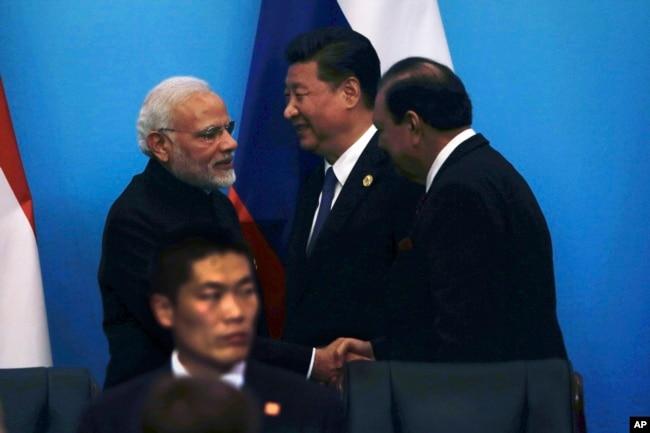在中國東部山東省青島舉行的上海合作組織峰會上,印度總理莫迪同巴基斯坦總統侯賽因握手,中國國家主席習近平在旁邊(2018年6月10日)。