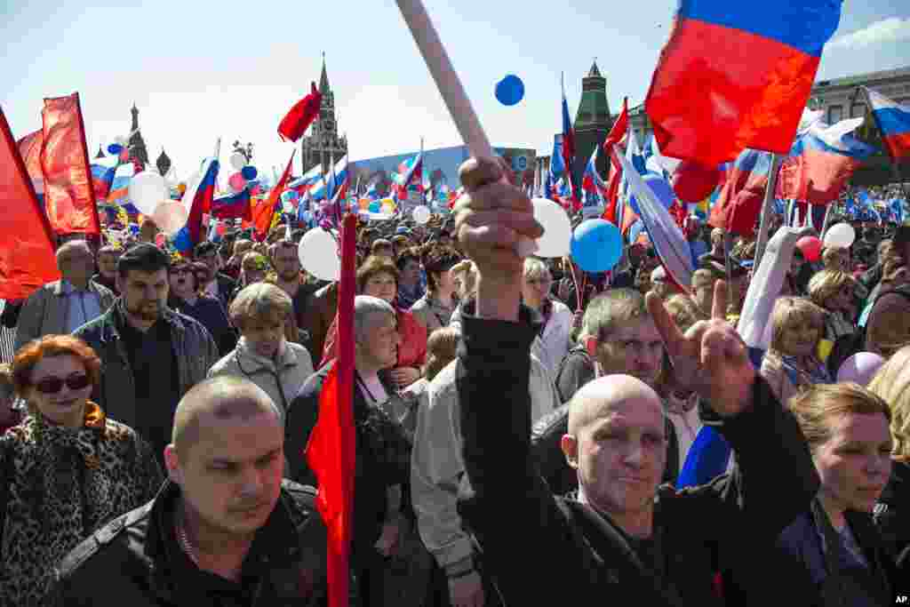 Russians wave flags and cheer as they walk on Red Square to mark May Day in Moscow, Russia, May 1, 2016. As in Soviet times, cheerful workers paraded across Red Square but instead of red flags with the Communist hammer and sickle, they waved the blue flag