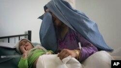 یوه افغانه مور روغتون کې له خپل ټپي ماشوم سره