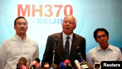 Malaysian Prime Minister Najib Razak (C) addresses reporters as Transport Minister Hishammuddin Hussein (L) and Department of Civil Aviation's Director General Azharuddin Abdul Rahman (R) stand by him, at Kuala Lumpur International Airport, March 15, 2014.