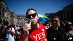 Seorang pendukung RUU pernikahan sesama jenis menunggu hasil referendum UU di depan istana Dublin, Irlandia (Foto: dok).