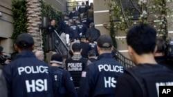 Agen federal memasuki sebuah kompleks apartemen yang diduga oleh aparat digunakan sebagai tempat bersalin oleh perempuan hamil yang berkunjung dari luar negeri di Irvine, California (3/3).