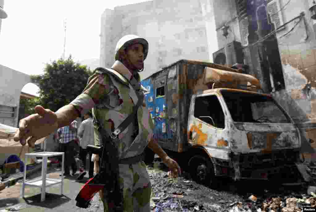 A soldier stands outside the burnt Rabaa Adawiya mosque, the morning after the clearing of a protest camp around the mosque, in Cairo, August 15, 2013.