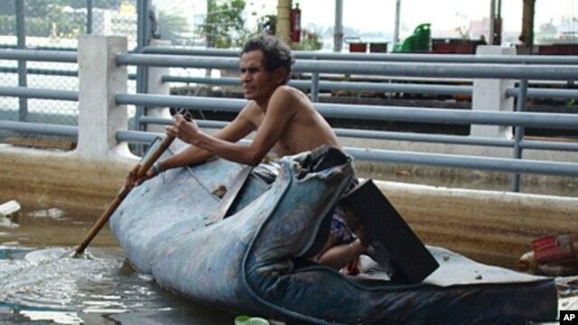 A Thai man on a mattress paddles along the Chao Phraya River which runs through Bangkok, Thailand, Nov 03, 2011.
