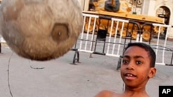 A boy plays soccer in front of army tanks at Abdeen Palace Museum in Cairo on Thursday.