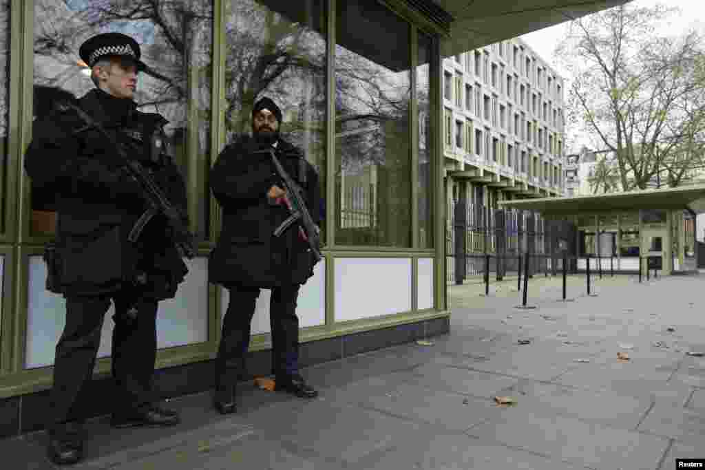 Police officers stand vigilant outside the U.S. embassy in London as the Senate Intelligence Committee prepares to release a report on the CIA's anti-terrorism tactics, Dec. 9, 2014.