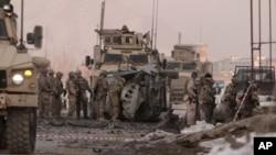 Des soldats américains fouillent le lieu où un kamikaze a percuté une voiture piégée contre un convoi de l'OTAN, tuant deux travailleurs civils étrangers, dans la capitale afghane Kaboul, en Afghanistan, le 10 février 2014. AP